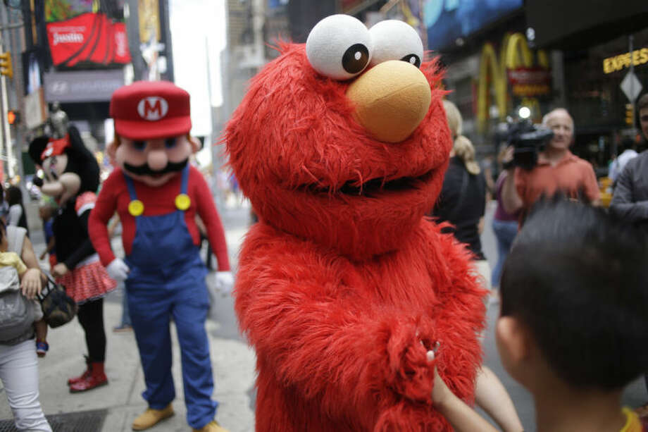 A person dressed as Elmo shakes hands with a pedestrian in Times Square on Monday, July 28, 2014 in New York. (AP Photo/Seth Wenig)