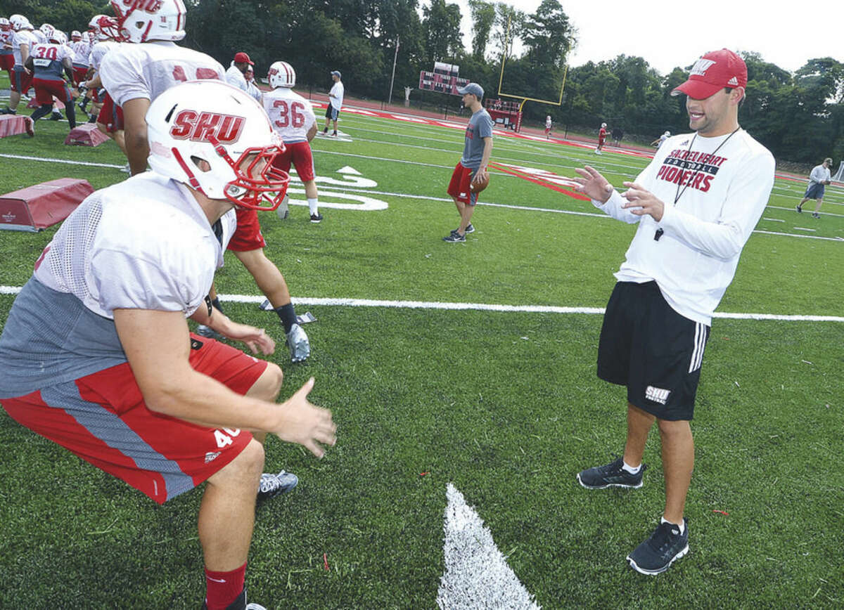 Hour Photo/Alex von Kleydorff Coach Mike Livingston works with the Sacred Heart University Pioneers during practice on Tuesday.