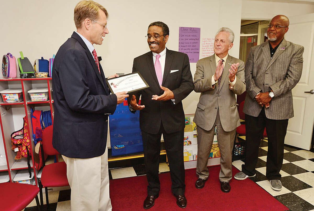 """Hour photo / Erik Trautmann CT Early Childhood Alliance Executive Director, Merrill Gay, honors State Representative Bruce Morris as one of the 26 legislators named 2015 """"Children's Champions"""" as Norwalk Mayor, harry Rilling, and Grace Baptiste Church Reverend, Lindsey Curtis, look on Thursday at Children's Playhouse Too."""