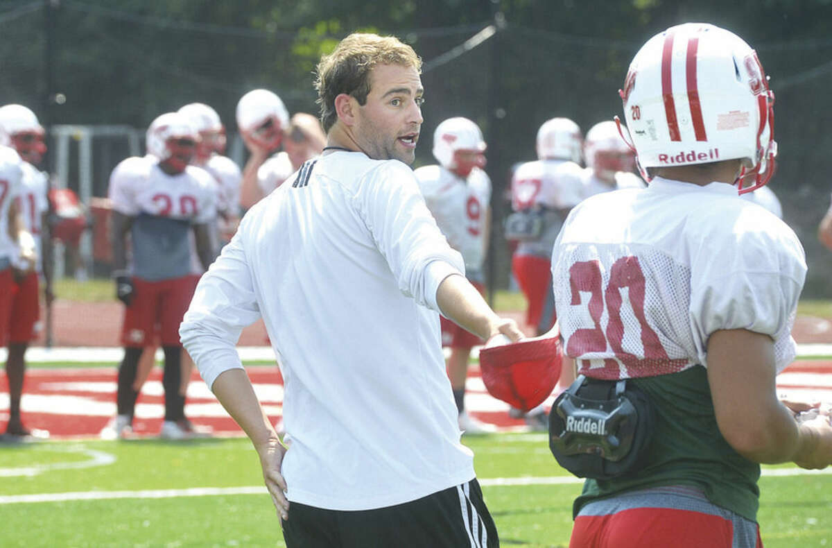 Hour Photo/Alex von Kleydorff Sacred Heart assistant football coach Mike Livingston works with Pioneers players during practice on Tuesday of game week at the Fairfield-based school. The Norwalk native, who has spent time as a graduate assistant at UConn and Boston College, is working through his first full-time season as a college football coach this fall.