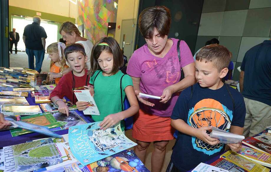 Hour Photo/Alex von Kleydorff Kelly Batzios helps family and friends Nicholas Ari Stizabal, Sofia Ari Stizabal and Jaden Tamburro pick out some books at their reading level at the Norwalk Reads book table during Back to School night at Stepping Stones Museum for Children