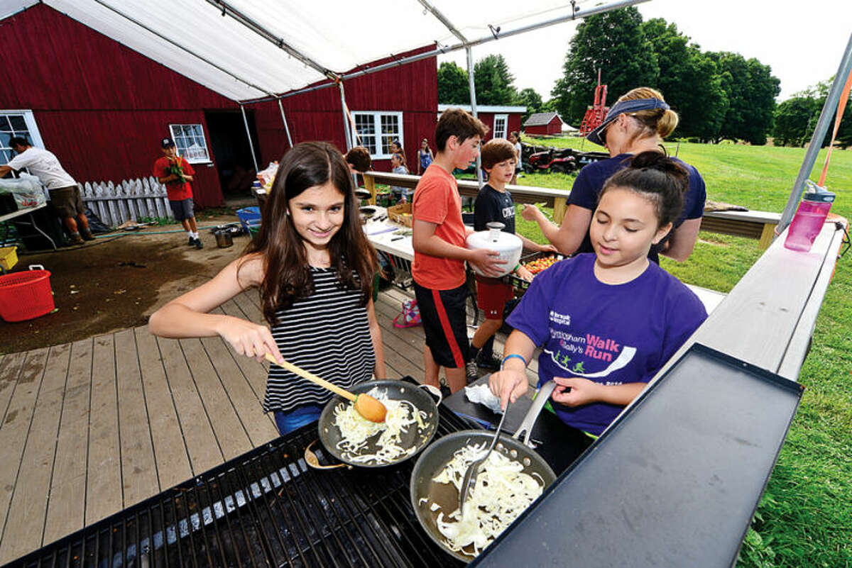 Juliette Sinor and Nicole Van Pelt caramelize onions for a flat-bread pizza during the Ambler Farm Farm-to-Kitchen program Tuesday.