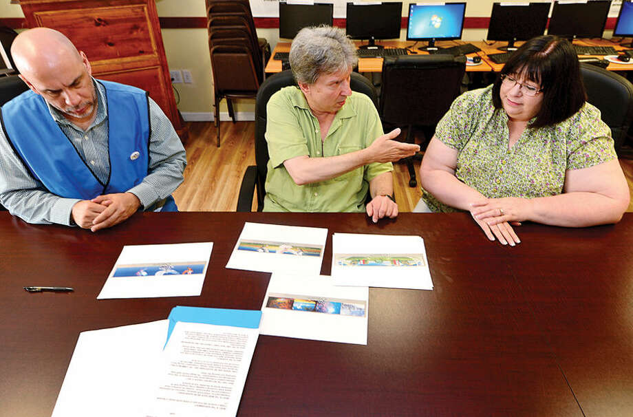 Hour photo / Erik Trautmann Creative Director of the Open Door Shelter's mural project, Rob Lokody, discusses the proposal with Operation Manager, Frank Concepcion, left, and Executive Director, Jeannette Archer-Simons, Friday at the shelter.
