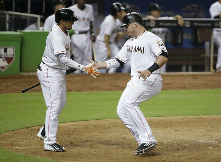 Miami Marlins' Justin Bour, right, is congratulated by Miguel Rojas after Bour scored on a sacrifice fly by J.T. Realmuto, during the fourth inning of a baseball game against the New York Mets, Friday, Sept. 4, 2015, in Miami. (AP Photo/Wilfredo Lee)