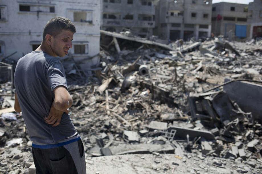 A Palestinian inspects a destroyed house in the heavily bombed Gaza City neighborhood of Shijaiyah, close to the Israeli border, Friday, Aug. 1, 2014. A three-day Gaza cease-fire that began Friday quickly unraveled, with Israel and Hamas accusing each other of violating the truce as seceral Palestinians were killed in a heavy exchange of fire in the southern town of Rafah. (AP Photo/Dusan Vranic)
