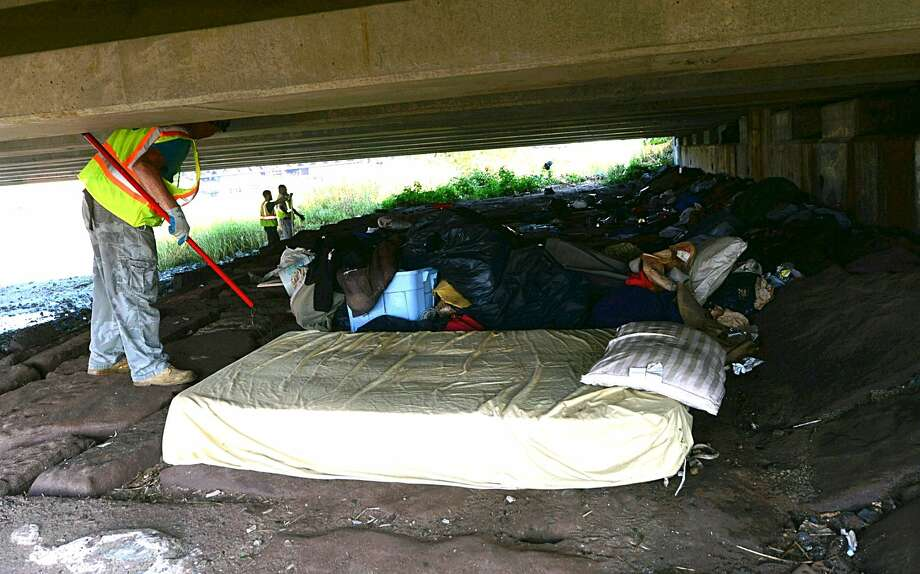 Norwalk DPW crews and Norwalk police remove a homeless encampment from underneath the Stroffolino Bridge Wednesday.