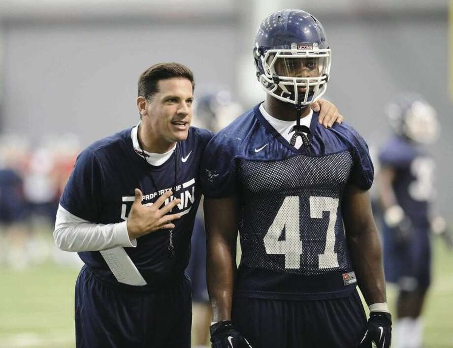AP photoUConn head coach Bob Diaco talks to player Reuben Frank during Saturday's practice.