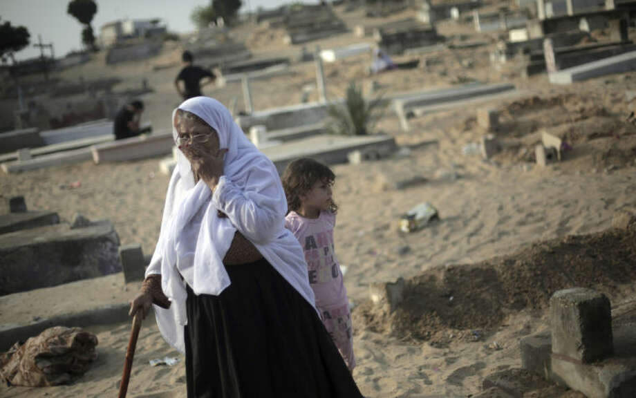 A Palestinian woman visits the graves of relatives marking the first day of Eid al-Fitr in a cemetery in Jabaliya refugee camp, northern Gaza Strip, Monday, July 28, 2014. Monday marked the beginning of the three-day Eid al-Fitr holiday, which caps the Muslim fasting month of Ramadan. Muslims usually start the day with dawn prayers and visiting cemeteries to pay their respects to the dead, with children getting new clothes, shoes and haircuts, and families visiting each other. (AP Photo/Khalil Hamra)