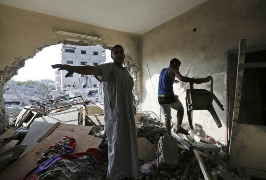 Palestinian members of the Abdel Al family salvage belongings from their house destroyed in an overnight Israeli strike in Gaza City in the northern Gaza Strip on Saturday, Aug. 2, 2014. (AP Photo/Lefteris Pitarakis)