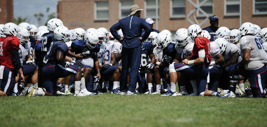 Connecticut head coach Bob Diaco, center, talks to his team at the end of an NCAA college football practice, Wednesday, Aug. 12, 2015, in Storrs, Conn. (AP Photo/Jessica Hill)