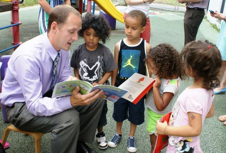 "Jack Dowling, AVP, business development officer at First County Bank, reads ""The Three Little Pigs"" to a captivated audience. The children are participants in the Head Start School Readiness Program at Armstrong Court, Greenwich which was visited by Greenwich Alliance for Education's Going Places With Books Story Mobile."