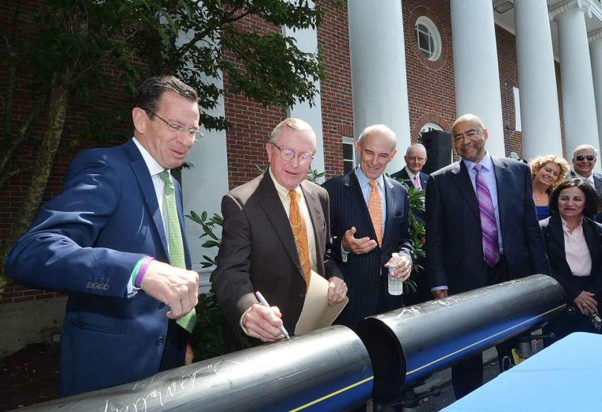 Hour Photo/Alex von Kleydorff Gov. Dan Malloy, watches Wilton First Selectman Bill Brennan sign a section of natural Gas Pipe with help from Northeast Utilities CEO Tom May and Yankee Gas President Rodney Powell. Brennan signed, then drew a dollar sign to show how much residents and businesses and the town might save with the new Natural gas line in Wilton