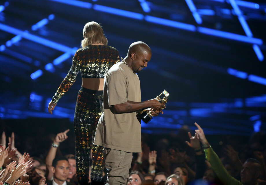 Taylor Swift, background, exits the stage after presenting the video vanguard award to Kanye West at the MTV Video Music Awards at the Microsoft Theater on Sunday, Aug. 30, 2015, in Los Angeles. (Photo by Matt Sayles/Invision/AP)