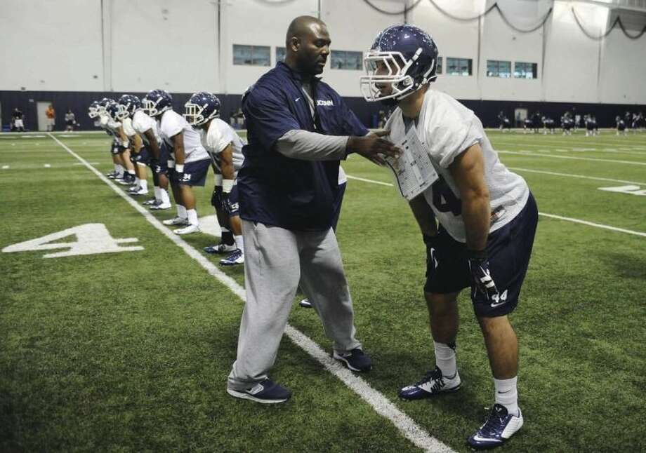 AP photoUConn coach David Corley, left, instructs Max DeLorenzo during the Huskies' season-opening practice Saturday.