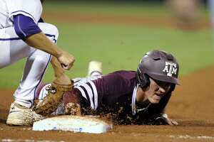 Texas A&M's Joel Davis dives back safely to first as TCU's Connor Wanhanen makes a late tag during the fourth inning of an NCAA college baseball tournament super regional game Saturday, June 11, 2016, in College Station, Texas. (AP Photo/Sam Craft)
