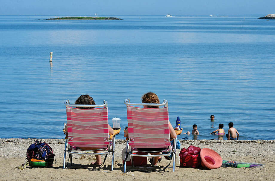 Hour photo / Erik Trautmann Kelly Franklin and Erika Weiss enjoy the beginning of the second half of summer at Calf Pasture Beach Tuesday.