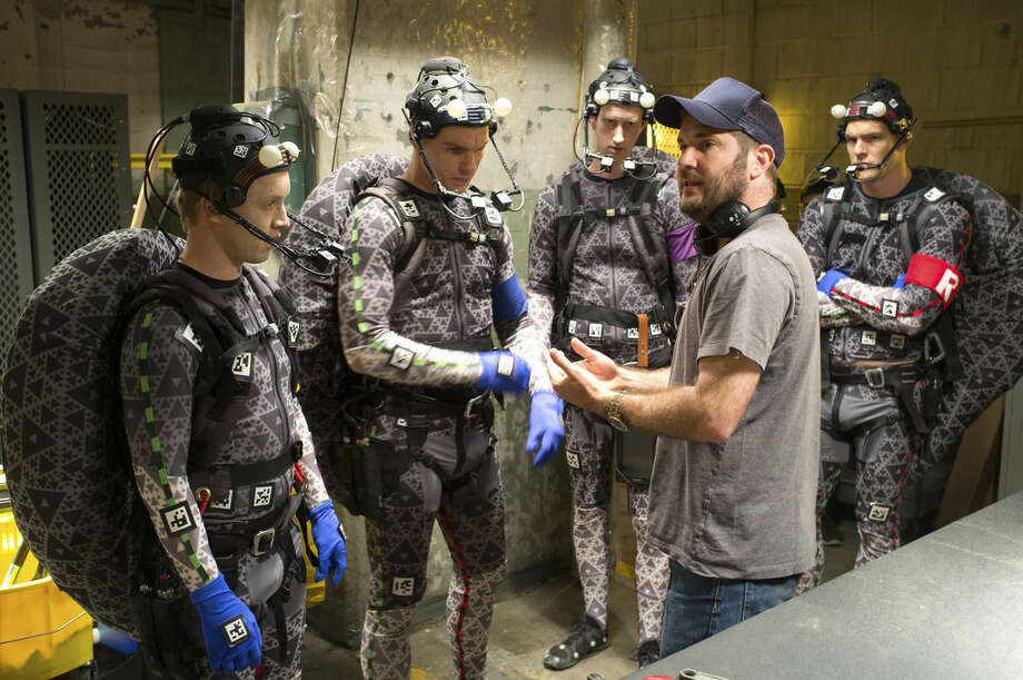 """This image released by Paramount Pictures shows director Jonathan Liebesman, foreground right, discussing a scene with actors portraying mutant ninja turtles, from left, Noel Fisher as Michelangelo, Pete Ploszek as Leonardo, Jeremy Howard as Donatello, and Alan Ritchson as Raphael during the filming of """"Teenage Mutant Ninja Turtles."""" (AP Photo/Paramount Pictures, David Lee)"""