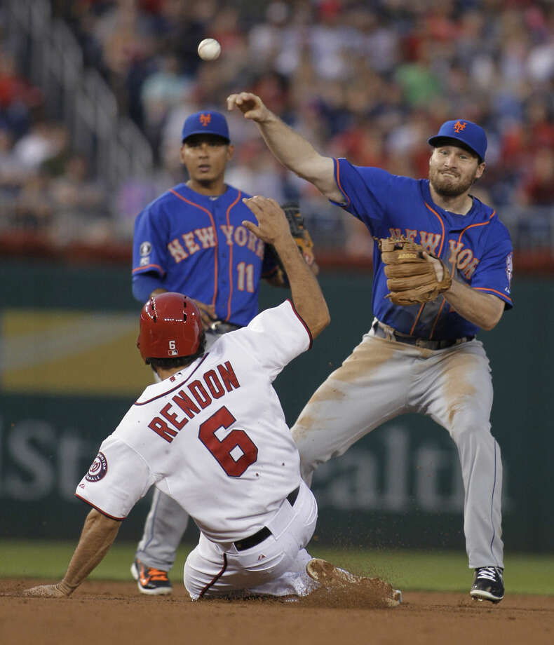 New York Mets second baseman Daniel Murphy throws to first on a double play, over Washington Nationals' Anthony Rendon, as shortstop Ruben Tejada watches during the third inning of a baseball game, Tuesday, Aug. 5, 2014, in Washington. Jayson Werth was out at first. (AP Photo/Luis M. Alvarez)