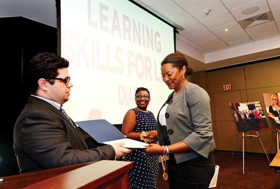 Hour photo / Erik Trautmann Bartender Academy graduate Debra Lyn Bennett receives her diploma from instructor Michael Barone, left, as Diageo's Hospitality Training Program, Learning Skills for Life, graduates 13 women during a ceremony at Diageo headquarters in Norwalk Wednesday.