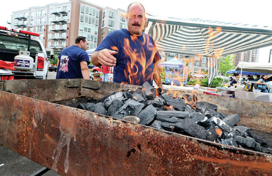 Hour photo / Erik TrautmannFirefighter Pete Cogliano of the Belltown Fire Department fires up the grill at Saturday's barbecue showdown at Fairway Market in Stamford. / (C)2013, The Hour Newspapers, all rights reserved