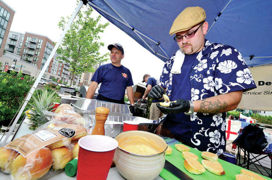 Westport Lt Brett Kirby and firefighter Joe Arnson prepare one of their dishes at the Firefighter BBQ Grilling Throw Down Saturday at Mairway Farket in Stamford.Hour photo / Erik Trautmann / (C)2013, The Hour Newspapers, all rights reserved