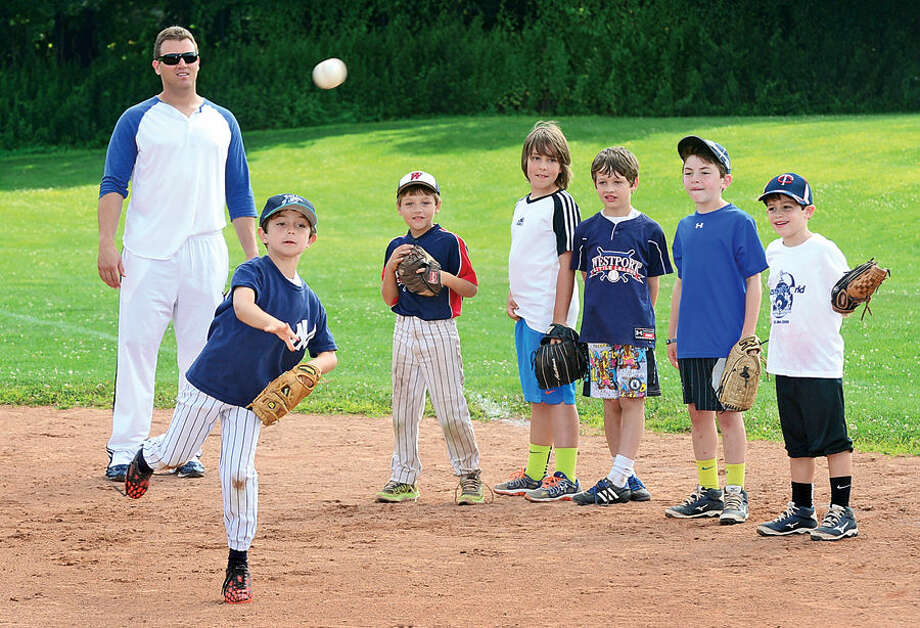 Hour photo / Erik Trautmann Sean Burroughs, former LLWS star and pro player now playing with Bport Bluefish, works with campers including Aaron Kail, 8, at Baseball World Camp on Wednesday,