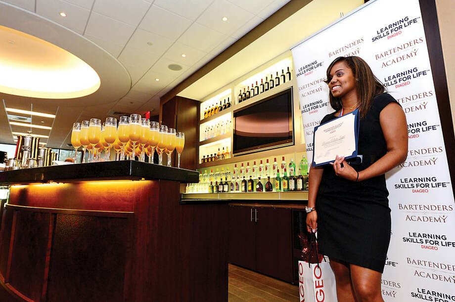 Hour photo / Erik Trautmann Bartender Academy graduate Celeste Lugo poses with her diploma as Diageo's Hospitality Training Program, Learning Skills for Life, graduates 14 women during a ceremony at Diageo headquarters in Norwalk Wednesday.