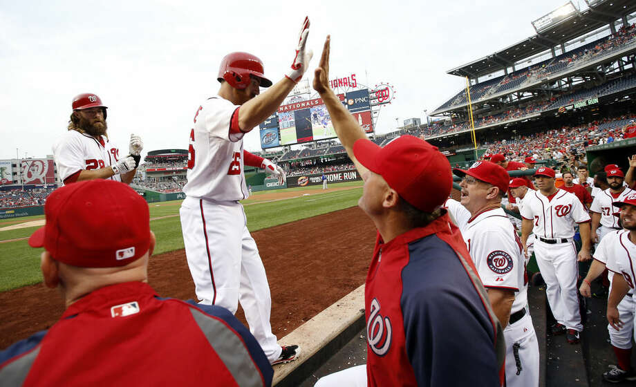 Washington Nationals' Adam LaRoche celebrates his two-run homer with bench coach Randy Knorr, and others, during the first inning of a baseball game against the New York Mets at Nationals Park Wednesday, Aug. 6, 2014, in Washington. (AP Photo/Alex Brandon)