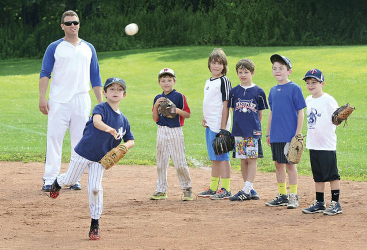 Hour photo / Erik Trautmann Sean Burroughs works with campers at Baseball World camp in Westport Wednesday.