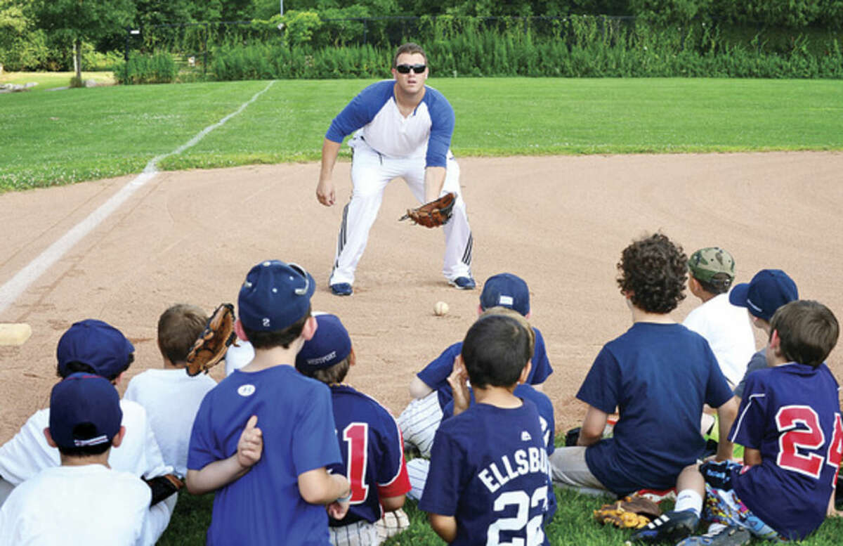 Hour photo / Erik Trautmann Former Major Leaguer and current Bluefish Sean Burroughs works with campers at Baseball World camp in Westport Wednesday.