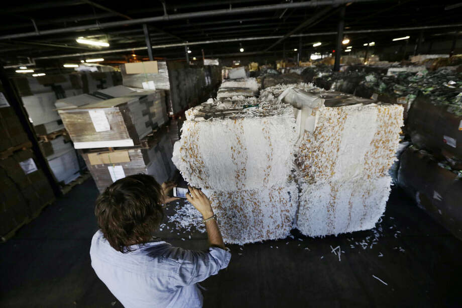 """TerraCycle Inc. founder Tom Szaky photographs large bales of recycled cigarette butts in a warehouse Tuesday, Aug. 5, 2014, in Trenton, N.J. Founded in 2001 by then-20-year-old Princeton student Szaky, TerraCycle works to collect and transform a range of hard-to-recyle items, from potato chip bags to cigarette butts, into colorful consumer products. A new reality show launching Aug. 8 will focus on the New Jersey-based recycling company. The reality docu-drama called """"Human Resources,"""" chronicles what it's like to work at the Trenton-based company. (AP Photo/Mel Evans)"""
