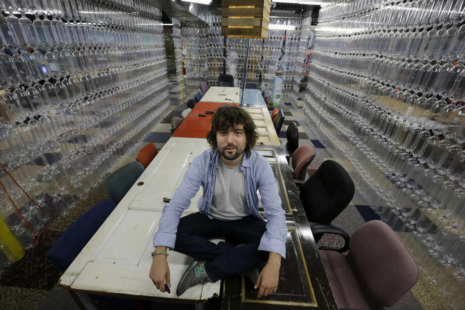 """AP Photo/Mel EvansTerraCycle Inc. founder Tom Szaky sits on a table made from old doors in a meeting room with walls of recycled soda bottles at the company Tuesday, Aug. 5, in Trenton, N.J. Founded in 2001 by then-20-year-old Princeton student Szaky, TerraCycle works to collect and transform a range of hard-to-recyle items, from potato chip bags to cigarette butts, into colorful consumer products. A new reality show launching Aug. 8 will focus on the New Jersey-based recycling company. The reality docu-drama called """"Human Resources"""" chronicles what it's like to work at the Trenton-based company."""