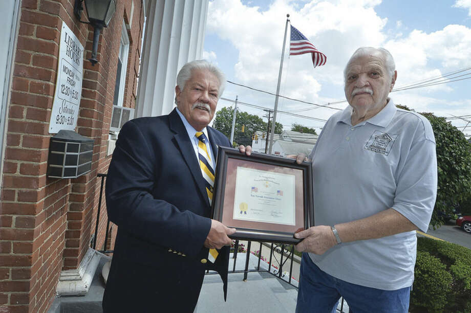 Hour Photo/Alex von Kleydorff Ed Isaacs with the Sons of The American Revolution, Roger Sherman Branch, presents a plaque for patriotism for displaying the American Flag to East Norwalk Association Library Executive Director Stanley Siegel