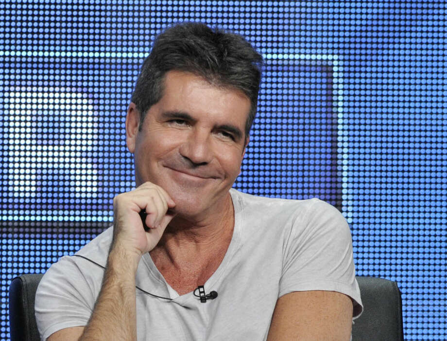 "FILE - This Aug. 1, 2013 file photo shows Simon Cowell, a judge on the ""The X Factor,"" smiles from the stage during a panel discussion on the show at the FOX 2013 Summer TCA press tour in Beverly Hills, Calif. The British edition of ""The X Factor"" is coming to U.S. television. Music entertainment cable channel AXS TV said Wednesday, Aug. 6, 2014, it will begin airing the singing contest's 11th season on Labor Day weekend. ""X Factor"" creator Simon Cowell is on the judging panel, which includes ex-Spice Girl Mel B and pop singer Cheryl Fernandez-Versini, formerly known as Cheryl Cole. (Photo by Chris Pizzello/Invision/AP, File)"