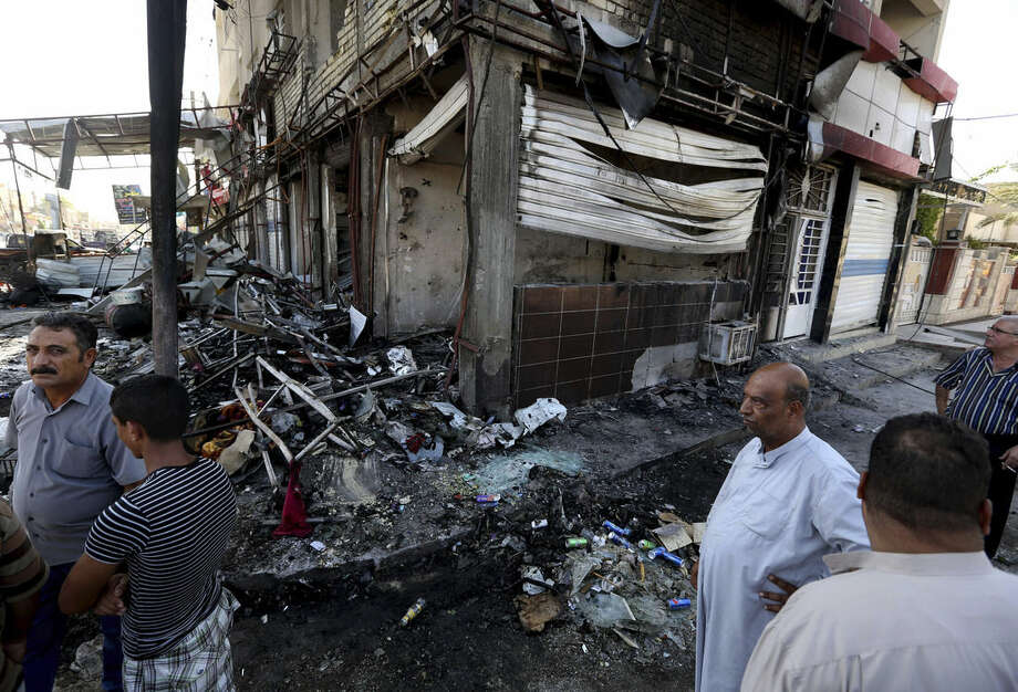 Civilians inspect damages the morning after a string of car bombs tore through busy shopping streets in several neighborhoods in Baghdad, Iraq, Thursday, Aug. 7, 2014. At least 50 people were killed on Wednesday as the army announced that one of its airstrikes had killed tens of militants in the northern city of Mosul. (AP Photo/Hadi Mizban)
