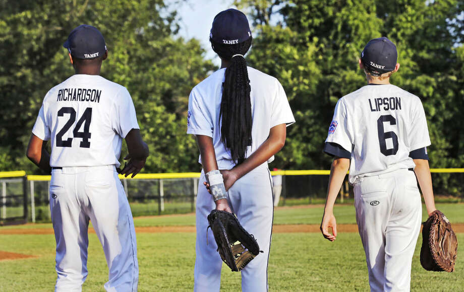 In this Aug. 6, 2014 photo, Pennsylvania's Mo'Ne Davis, center, stands with teammates Joe Richardson (24) and Erik Lipson (6) prior to facing the District of Columbia in a baseball game in the Little League Eastern Regionals at Breen Stadium in Bristol, Conn. Davis and New Jersey's Kayla Roncin are competing to make it to the Little League World Series, a rare feat for girls. (AP Photo/Charles Krupa)