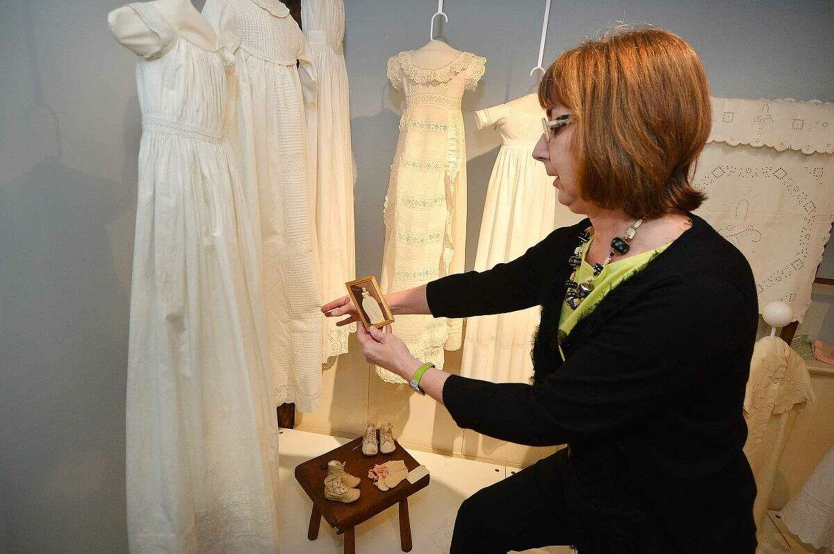 Allison Sanders places a photograph of Wilton's William Evans wearing the christening gown from 1872 that is part of the new exhibit White Linen and Lace on view at the Wilton Historical Society.
