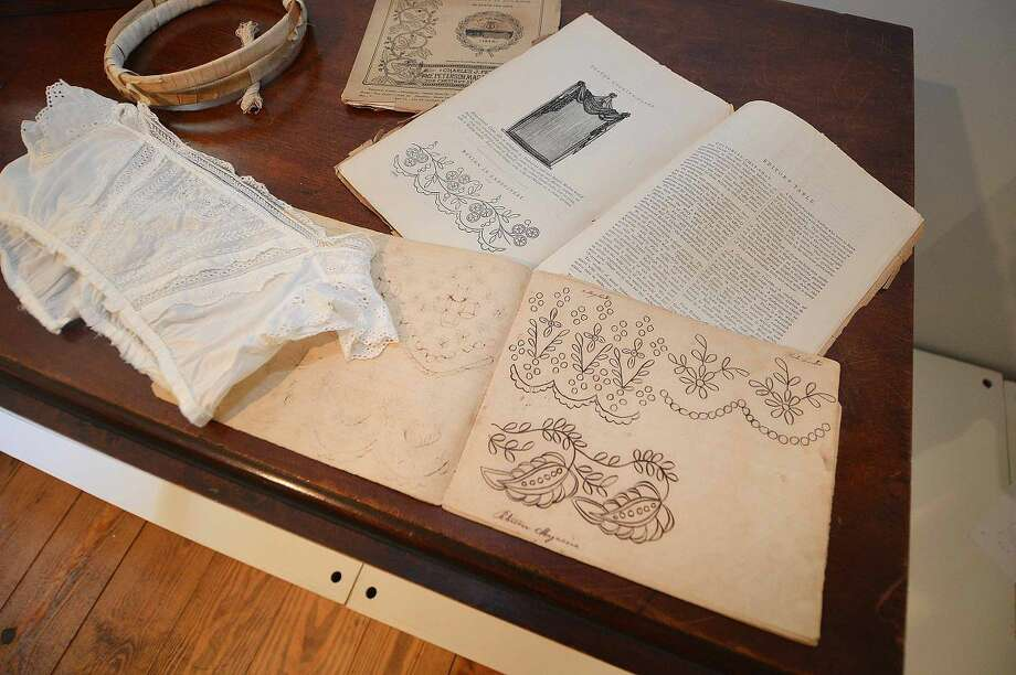 Pattern books with the finished piece of clothing are part of the new exhibit White Linen and Lace Baby Clothing 1800-1950