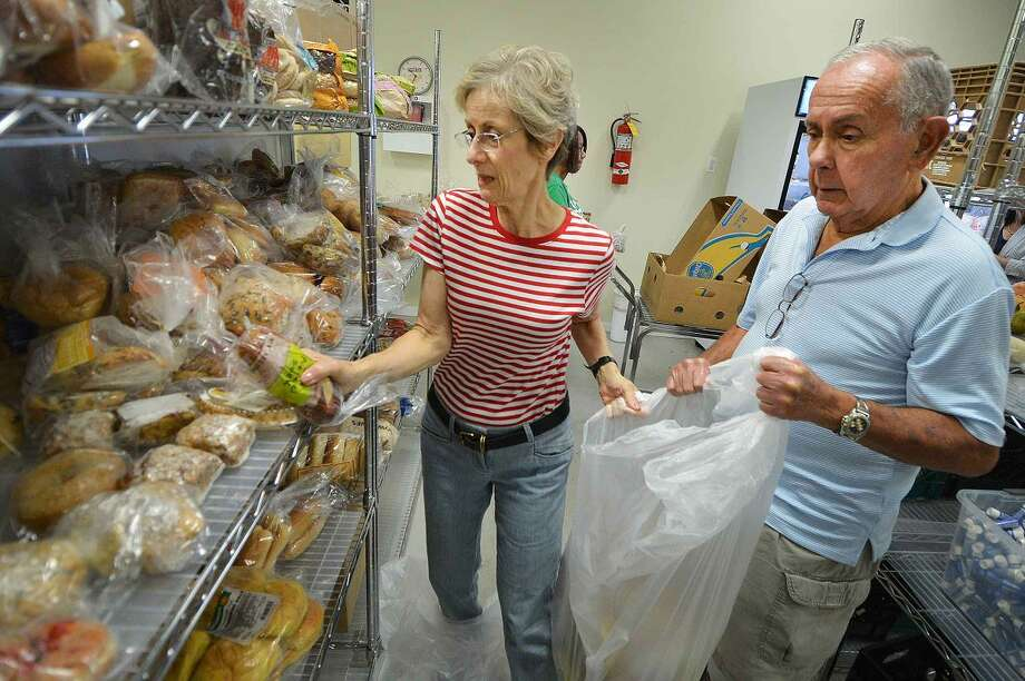 Hour Photo/Alex von Kleydorff Volunteers Nancy Hanze and Ira Miller stock the shelves with donated bread and rolls from the Community Pantries program at Person to Person.