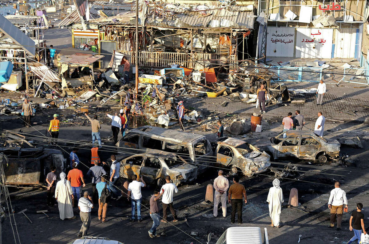 Iraqi civilians gather the morning after a string of car bombs tore through busy shopping streets in several neighborhoods in Baghdad, Iraq, Thursday, Aug. 7, 2014. At least 50 people were killed as the army announced that one of its airstrikes had killed tens of militants in the northern city of Mosul. (AP Photo/Karim Kadim)
