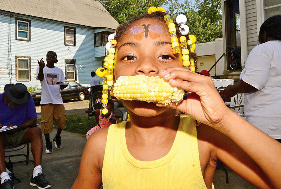 Hour photo / Erik Trautmann Zaniya McFadden, 6, enjoys corn on the cab during the Bouton St. Back to School Block Party Saturday.