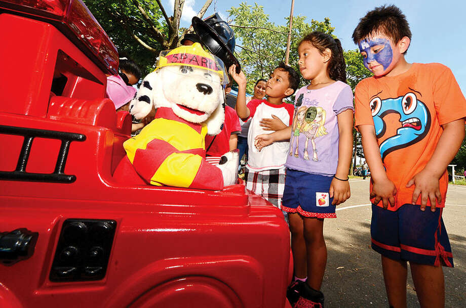 Hour photo / Erik Trautmann Edward Recinos, Vanessa Sanchez and Ian Arriaga a greetd by Sparky the robot fire dog during the SoNo Day Out at Ryan Park sponsored The Norwalk Police Department Community Services Division.