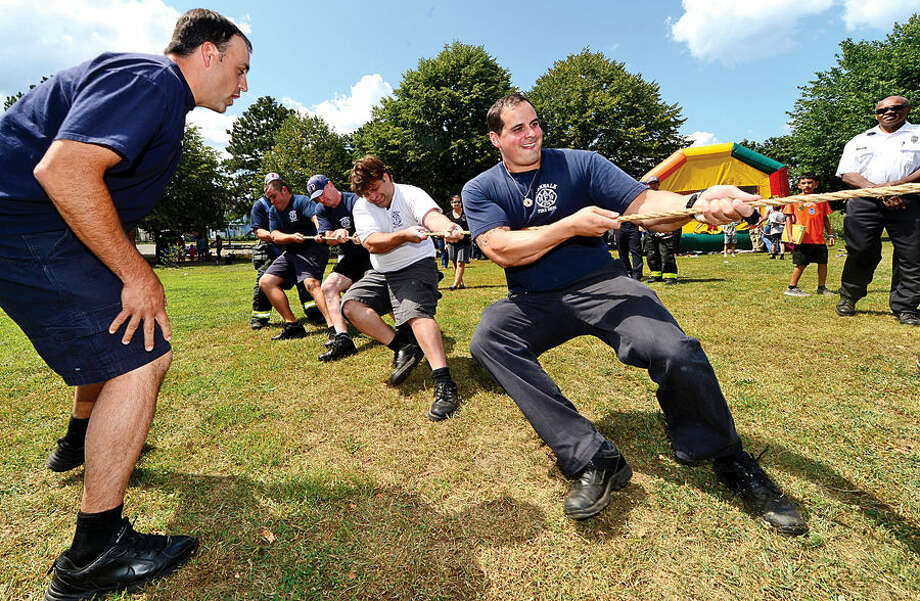 Hour photo / Erik Trautmann Firefighter Whitney King gets encouragement from fellow firefighter Mark Schimento a tug-o-war competition with the Norwalk Police Department during the SoNo Day Out at Ryan Park Saturday sponsored The Norwalk Police Department Community Services Division.