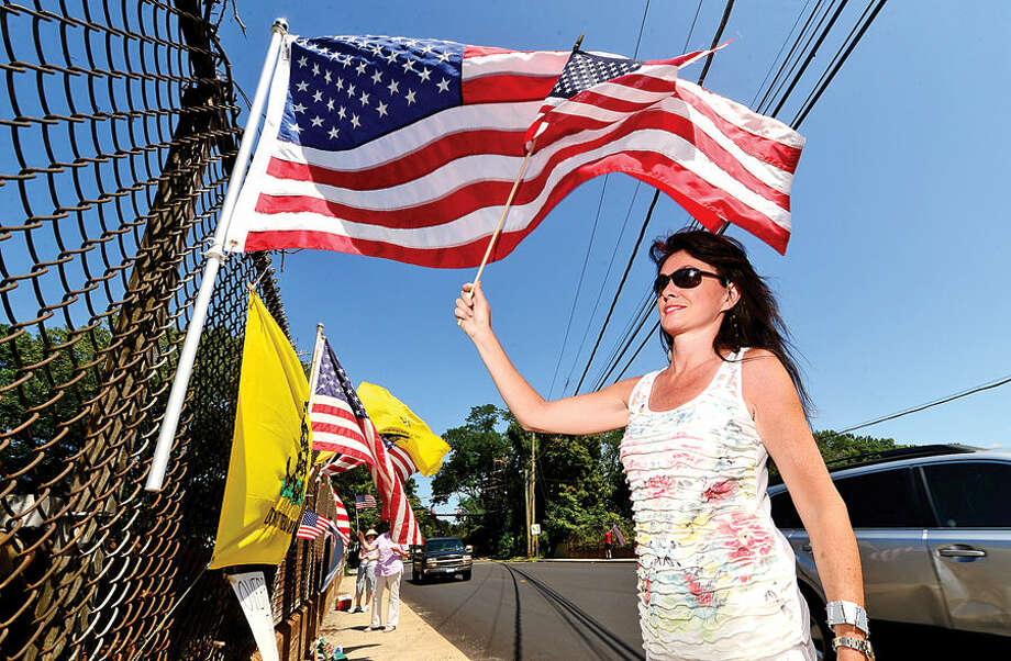 Hour photo / Erik Trautmann Area residents with Overpasses for America including Brenda Gaffney protest the immigration policy of the Obama administration on the I-95 overpass on Stawberry Hill Ave in Norwalk Saturday.