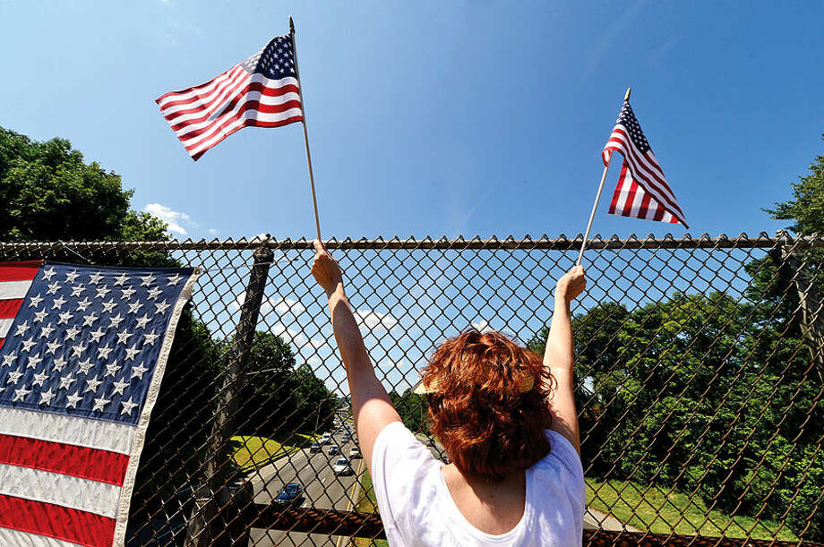 Hour photo / Erik Trautmann Area residents with Overpasses for America protest the immigration policy of the Obama administration on the I-95 overpass on Stawberry Hill Ave in Norwalk Saturday.