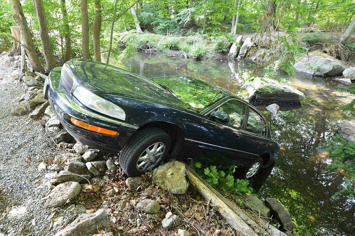 Hour Photo/Alex von Kleydorff A Buick sits perced on the banks of the Five Mile River off Bonnybrook Tr. on Monday morning