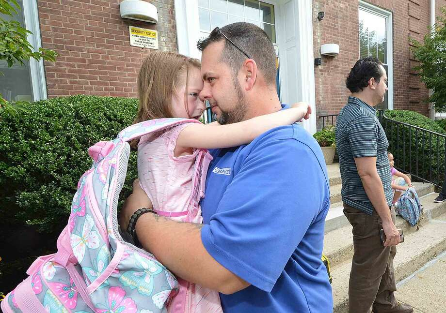 Hour Photo/Alex von Kleydorff Keith Zarembski gives his daughter 7yr old Madison a hug before she is on to the 2nd grade at Columbus Magnet School on Monday morning