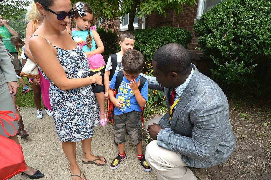 Hour Photo/Alex von Kleydorff Columbus Magnet School Principal Medard Thomas makes it easy for students to head in for the first day of school at Columbus Magnet School on Monday