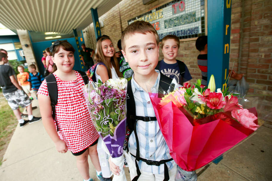 Hour photo/Chris Palermo. Alexander Enders holds flowers for his teacher and principal alongside his fellow 5th graders Isabella Boucher, Robert Boucher, and Chloe Zako for the first day of school at Naramake Elementary Monday morning.