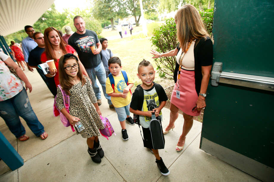 Hour photo/Chris Palermo. Shane McMarthy and his sister Angelina Fuentez smile as they walk in for the first day of school at Naramake Elementary Monday morning.